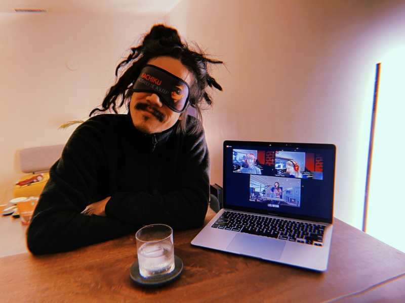 Photo of myself (wearing a Hachiku sleeping mask) with my laptop and a beverage.